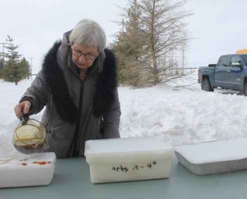 Sylvia Dion pouring Maple Syrup on snow during Zenon Park Winter Carnival