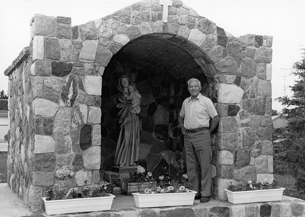 Stonecutter Henri Poulin near grotto he built