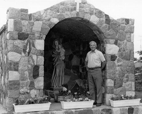 Stonecutter Henri Poulin near grotto he built